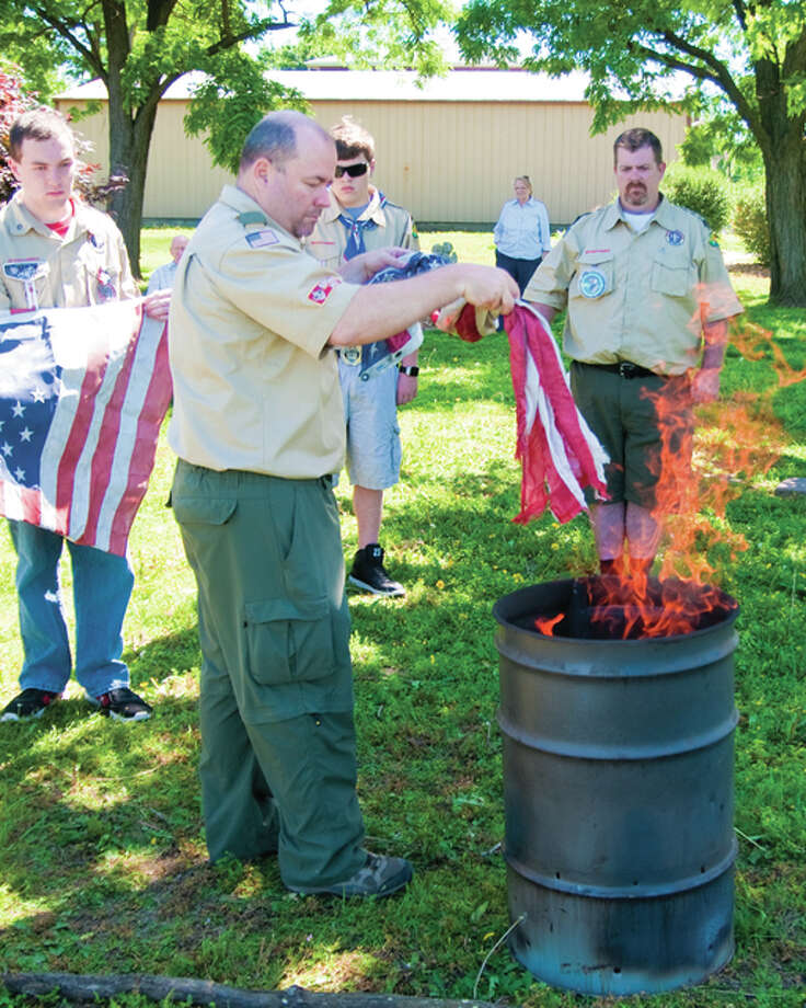 Boy Scout Troup 777 leader Mark Smith lowers into a fire one of the many tattered American flags that was donated for the Memorial Flag Retirement ceremony that took place at Wanda United Methodist Church's prayer garden Sunday in Roxana.