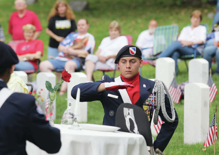 "Cadet Lt. Col. Tristan Counts, a member of the Alton High School Air Force Junior ROTC, performs a ""Table Top Ceremony"" during the 11th annual Memorial Day Sunset Ceremony in honor of those missing in action."