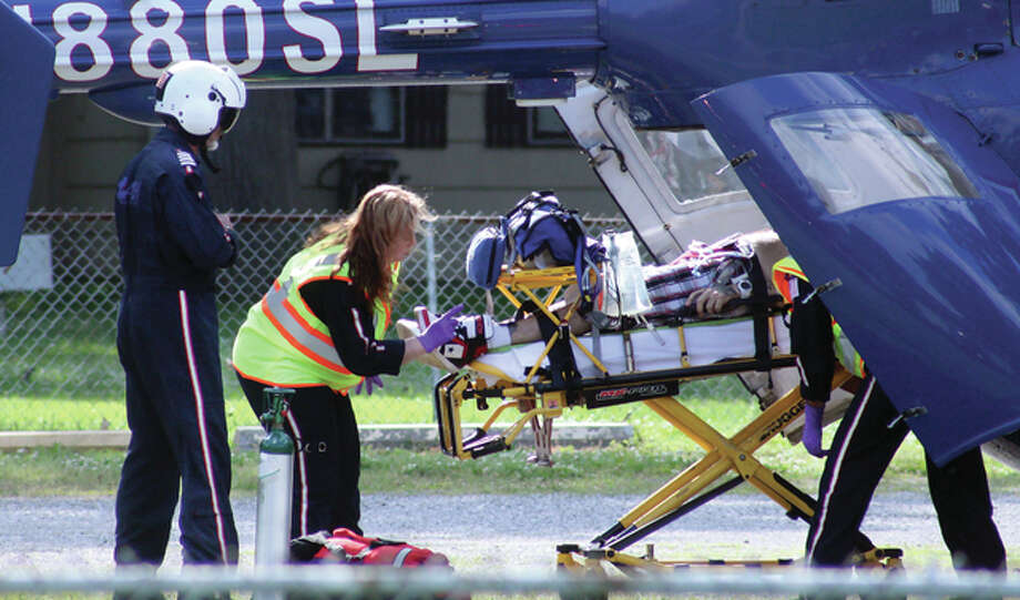 An ARCH Air Medical Services helicopter pilot, left, watches as paramedics load a man into the helicopter after he was shot in the chest Tuesday afternoon. The helicopter landed at South Roxana Dads Club Park, a few blocks away from where police officers had set up a crime scene on Smith Avenue.