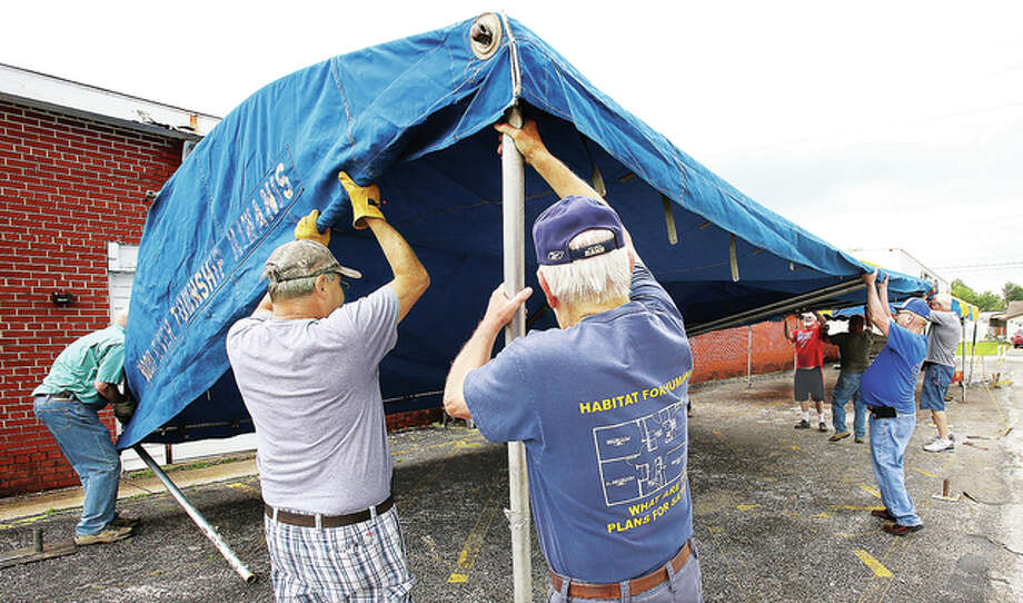 Members of the Kiwanis Club of Wood River Township set up one of their tents for their barbecue on the lot of the former Hutton Ford body shop on Illinois Route 111 in Wood River. The club recently lost its long-time location just east of the site.