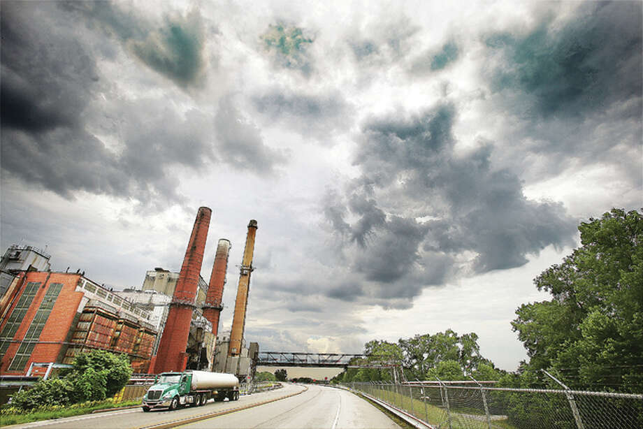 The Dynegy, Inc.-operated power plant, left, in East Alton is set to permanently close Wednesday. Storm clouds hovered overhead Tuesday as upwards of 90 jobs were about to be eliminated by the shutdown of the 1950s-era, coal-fired power plant. The company cites unfair market conditions and the lack of need for the plant as the reasons it is closing. The plant was once a critical part of powering the Alton area's industries for nearly three decades, allowing the Riverbend to grow into the third-largest industrial district in the state by the early 1970s. Most of those industries are gone or greatly reduced in size and output.