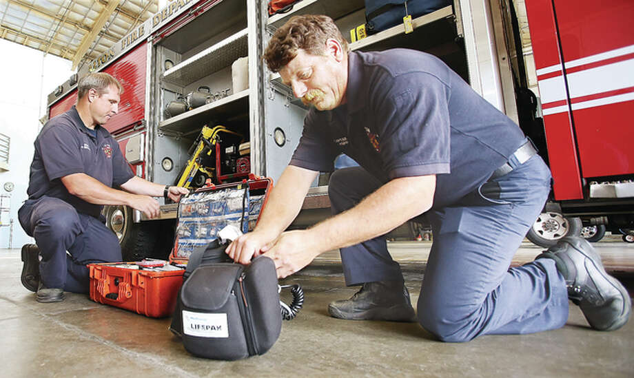 Alton firefighter-paramedics check their equipment every day like engineer Michael Shewmaker, left, and Capt. Jeffrey Knipp, right, on the pumper at Alton Fire Station No. 1. The city of Alton announced Wednesday that the fire department will soon begin staffing two fire department ambulances, a trend that has been common in the fire service for more than two decades. There will be one ambulance at each of Alton's two fire stations.