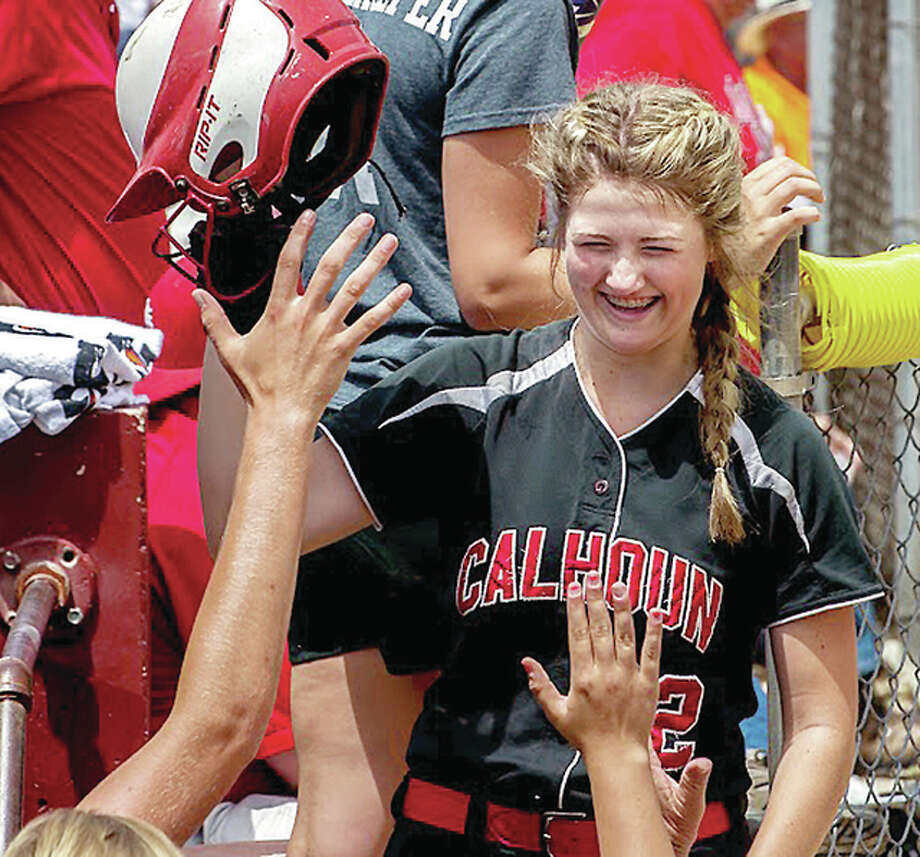 Calhoun freshman Sophie Lorton is greeted in the Warriors dugout in the 17th inning Friday after scoring a run following her bases-loaded triple that broke open a scoreless game Friday in the Class 1A state semifinals in East Peoria. Photo: Michael Weaver | For The Telegraph
