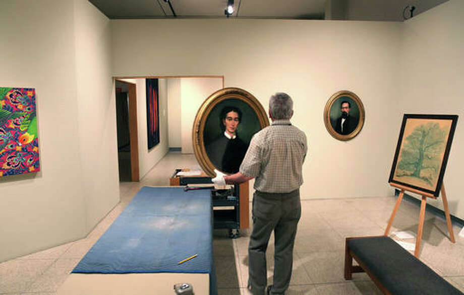 In this June 2, 2016 photo, Illinois State Museum employee Phil Kennedy prepares to hang a reverse painting on glass portrait of Prudence Capps Beidler from 1867 in the museum in Springfield, Ill. The museum could reopen soon, after being closed since October due to the state budget impasse. The state's Department of Natural Resources said the museum could reopen July 2, following approval of an admission charge to the main museum campus. (David Spencer/The State Journal-Register via AP)
