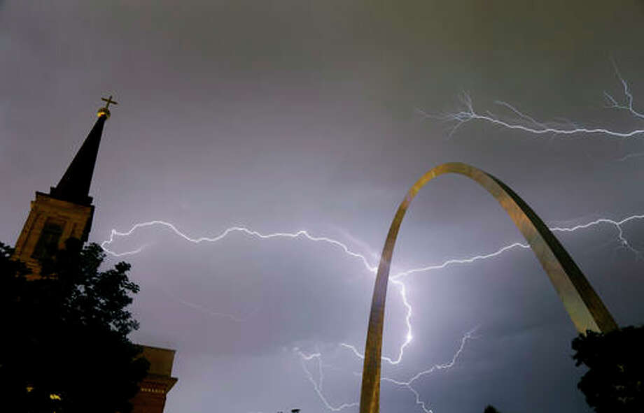 Lightning flashes in the sky behind the Gateway Arch, right, and Old Cathedral, left, as a line of thunderstorms moves through St. Louis, Wednesday, May 11, 2016. Thousands of Ameren Corp. customers in the St. Louis area are without power after the strong thunderstorm hit the region. (AP Photo/Jeff Roberson)