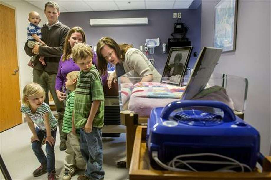 In this May 9, 2016 photo, Kyler Lange, left, leans in to listen as Sarah Greer, of the OSF St. Francis Medical Center Perinatal Supportive Care in Peoria, Ill., talks to her and her brothers, Weston, foreground, Dean, and Quintin, and their parents Aaron and Terra Lange, about the CuddleCot the family donated to the OSF Family Birthing Center. The CuddleCot is a specialized cooling device fitted for use in a bassinet that allows families to spend more time with a baby who is stillborn or dies shortly after birth. The Lange family had a daughter stillborn in March 2014.