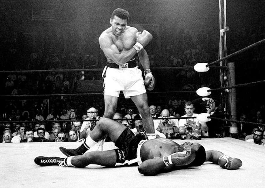 Heavyweight champion Muhammad Ali, then known as Cassius Clay, stands over challenger Sonny Liston, shouting and gesturing shortly after dropping Liston with a short hard right to the jaw, in Lewiston, Me. in this May 25, 1965 file photo. Ali was declared the winner. The bout lasted only one minute into the first round. Photo: John Rooney | AP Photo