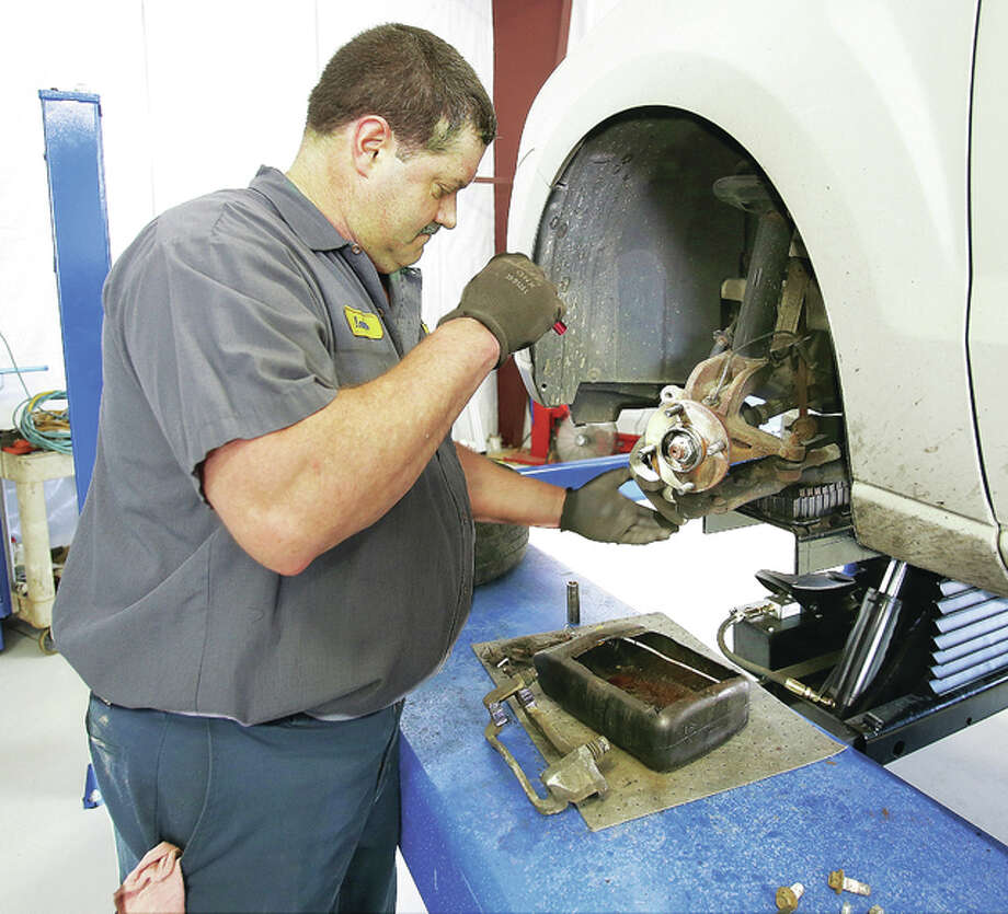 An employee at Pro Automotive Services in Wood River works on a car earlier this week. The shop is one of two in the nation chosen by the National Automotive Parts Association (NAPA) for renovations that include tech-savvy upgrades. Photo: John Badman   The Telegraph