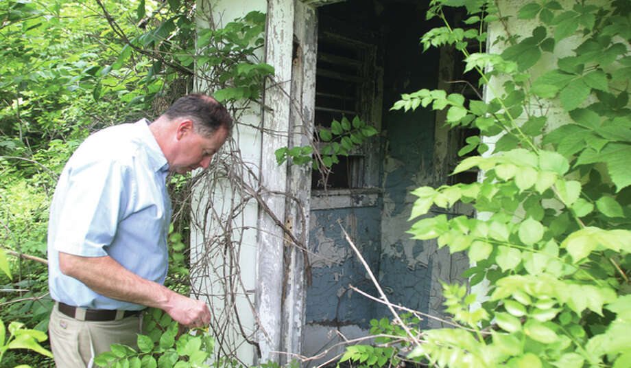 Illinois Department of Natural Resources employee Scott Isringhausen checks for rattlesnakes before going into the remains of a guard shack at the entrance to the radar site of a former Nike missile base in Pere Marquette State Park near Grafton. The base, largely forgotten, was part of a ring of more than 260 bases protecting the country against nuclear attack in the 1960s. Photo: Scott Cousins | The Telegraph