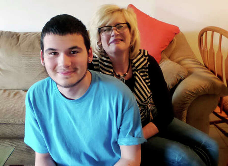 Philip Graceffa poses for a photo with his mother, Cynthia, at her home in Rockford. Graceffa recently finished the Redeploy Illinois program, which gives juveniles an option based in the community, instead of prison. Several Redeploy programs around the state are being cut because of the state budget impasse. Phillip says the program helped turn his life around after several bad decisions. He's now working at a local fast food restaurant, completing his high school equivalency and dreams of being a firefighter someday.