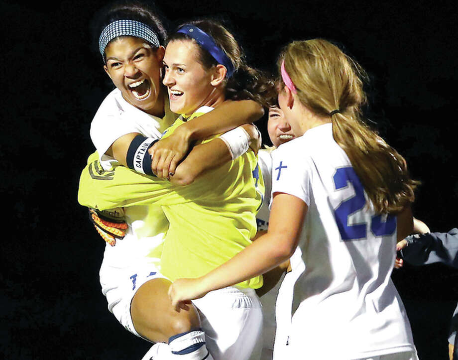 Marquette's Lauren Fischer, middle, hoists Adriana Schindler, left, in her arms as teammates celebrate after Fisher stopped the final penalty kick against Gibault during Wednesday's Sectional semi-final game played at McKendree College. Marquette won the game 1-0 on penalty kicks. Credit: Billy Hurst - For the Telegraph Photo: Billy Hurst File Photo | For The Telegraph