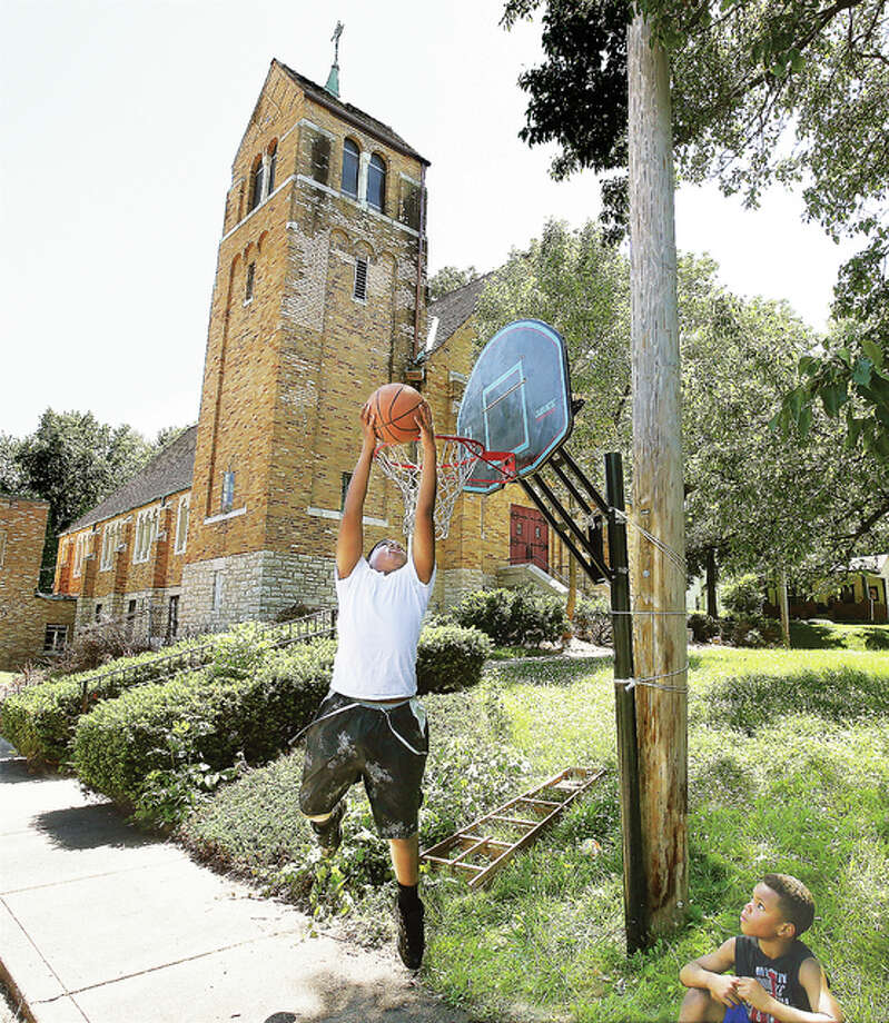 Members of the youth group at the new Mellenium Temple didn't waste any time setting up a basketball hoop on the parking lot of their new home in the former Trinity Lutheran Church at 801 Blair St. in Alton. The old church has been vacant for years.