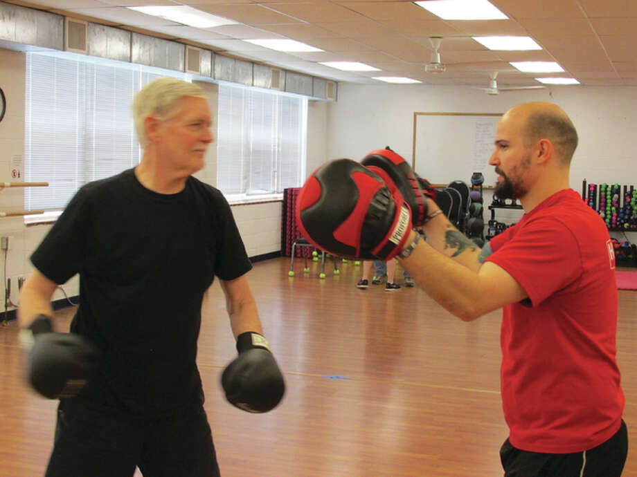 Rock Steady Boxing coach and Senior Services Plus Wellness Coordinator Lucas Hale with a Rock Steady Boxing participant.