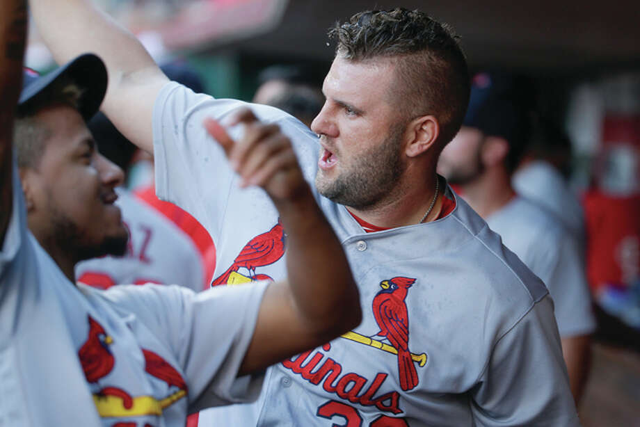 Cardinals first baseman Matt Adams (right) celebrates in the dugout with Carlos Martinez (left) after hitting a three-run home run in the first inning Wednesday night against the Reds in Cincinnati. Photo: Associated Press