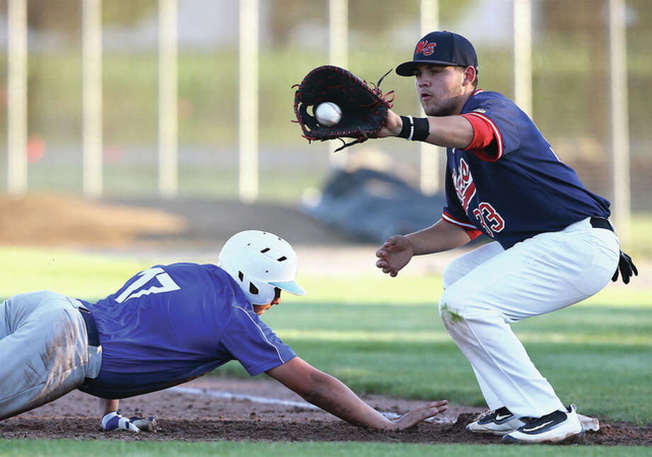 Metro East first baseman Jacob Kanallakan (right) takes a pickoff throw while Jerseyville's Collin Carey dives safely back into first base safely in a Senior Legion baseball game Thursday night at Ken Schell Field in Jerseyville. Metro East was in Greenville on Friday, winning two games to push its record to 4-0. Photo: Billy Hurst / For The Telegraph
