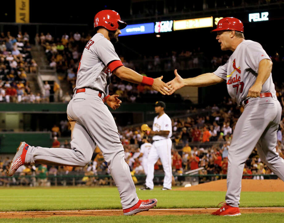 The Cardinals' Matt Carpenter (left) is greeted by third base coach Chris Maloney after hitting a three-run home run during the eighth inning Friday night in Pittsburgh. Photo: Associated Press
