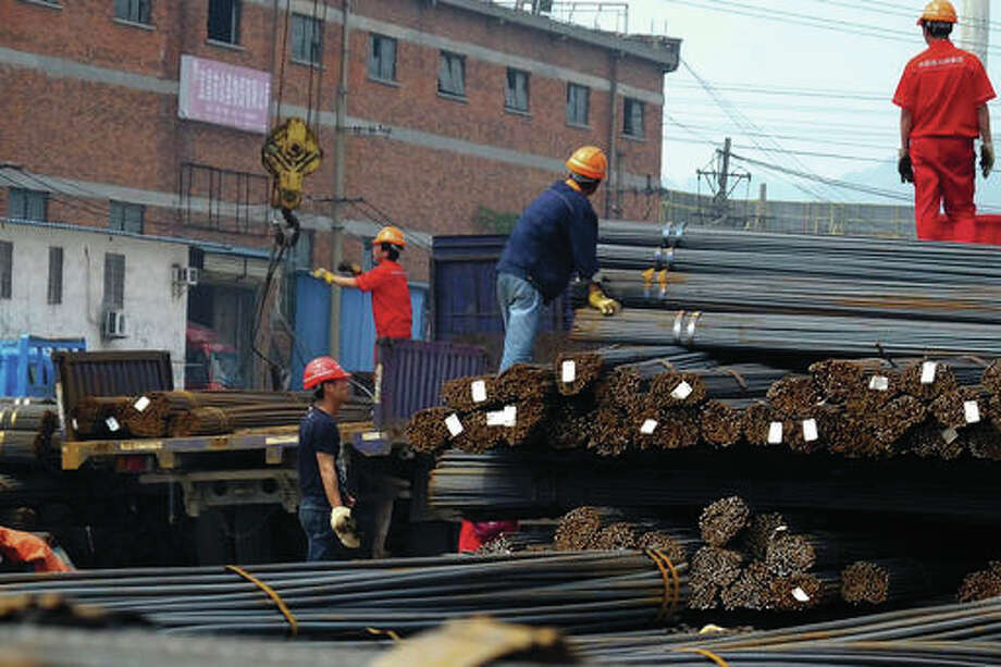 In this April 29, 2016 photo, workers load steel bars at a steel market in Yichang in central China's Hubei province. (Chinatopix via AP)