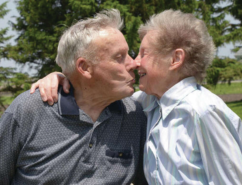 Marvin Wilke, plants a kiss on his wife Iva, 89, outside their farm house in Anchor, Ill. At 94 he still tills the ground on 80 of his 160 acres. A tenant farmer does the planting and harvesting.