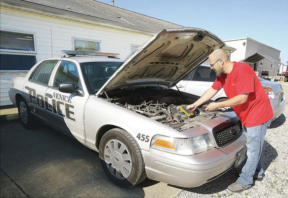 John Foiles, general manager of DataTronics, checks under the hood of a Venice police car this week at the company's new location at 7228 Herter Industrial Drive in Godfrey. The company deals with a number of two-way radio related business including the systems installations for police cars across the area. They relocated from a space on East Broadway in Alton a few months ago. Photo: John Badman | The Telegraph