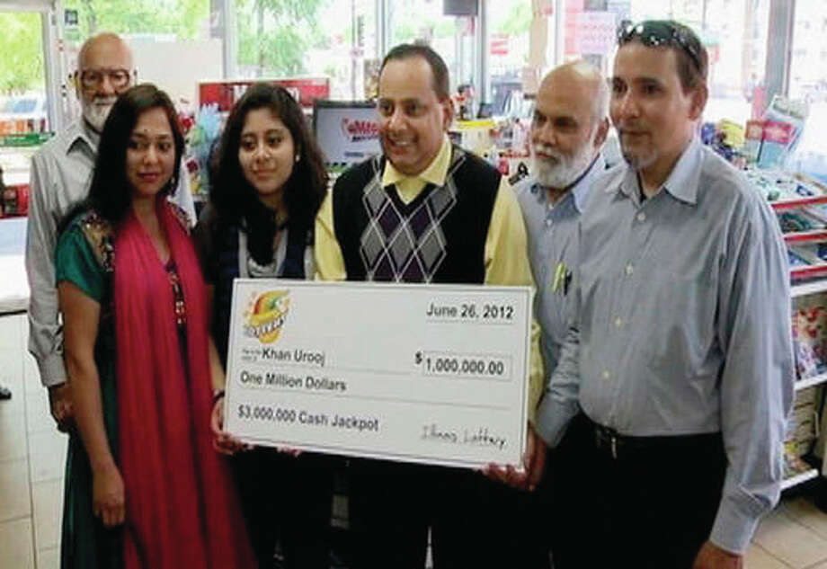 This June 2012 file photo provided by WMAQ-TV in Chicago, shows Urooj Khan, center, holding a ceremonial check in Chicago for $1 million as winner of an Illinois instant lottery game. At left, is Khan's wife, Shabana Ansari. Khan died suddenly on July 20, 2012, just days before he was to collect his winnings. With his departure from office this week, Stephen Cina, the former Cook County medical examiner leaves behind a beguiling mystery that he set in motion with a sensational declaration three years ago that Khan was poisoned with cyanide.