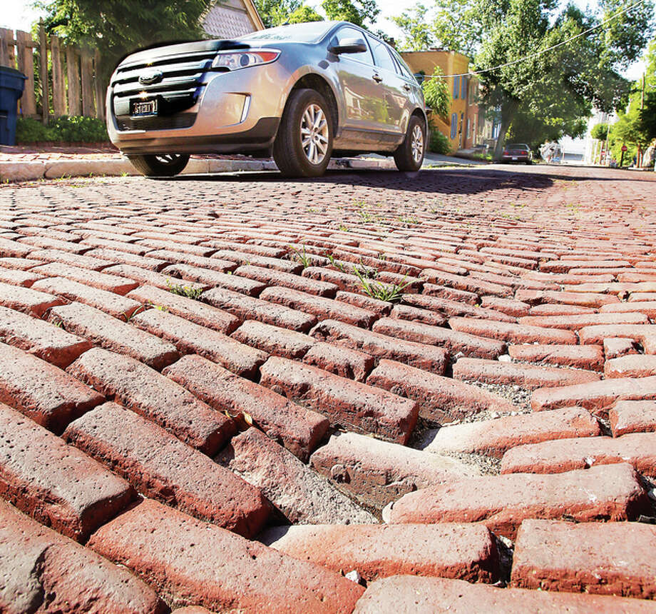 A car passes up William Street in Alton Thursday past the sinking bricks that run down the center of the street from underground subsidence. The strip of bad bricks on William, from Bond Street south to West Broadway, are the subject of a $1 million grant Alton is seeking to overhaul the street.