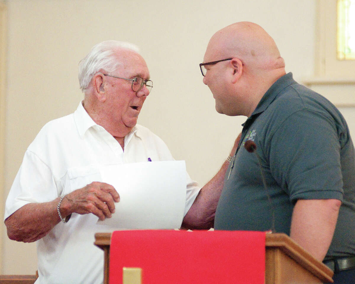 Dale Ragus, left, accepts a certificate of appreciation from First Baptist Church of Wood River Rev. Bob Kirbach, after Kirbach acknowledged that Ragus was the longest living member of the church who was baptized in 1937.