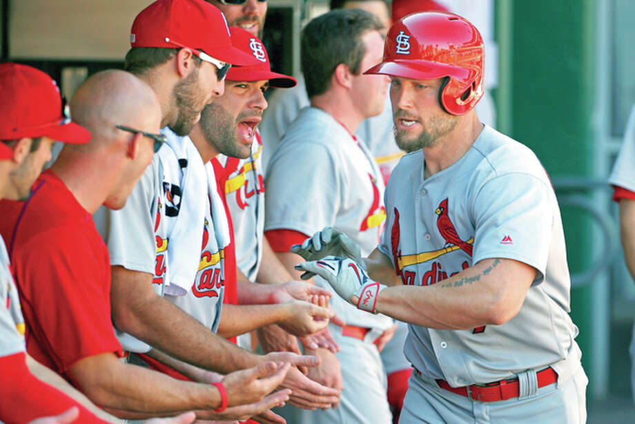 The Cardinals' Matt Holliday, right, celebrates with teammates in the dugout after hitting a solo home run off Pirates starting pitcher Jonathon Niese in the first inning Sunday in Pittsburgh. Photo: AP Photo