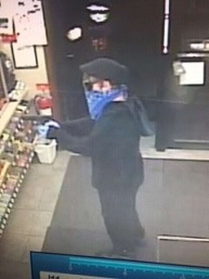 One suspect stands at the door during the robbery, while another approaches the counter as pictured here.