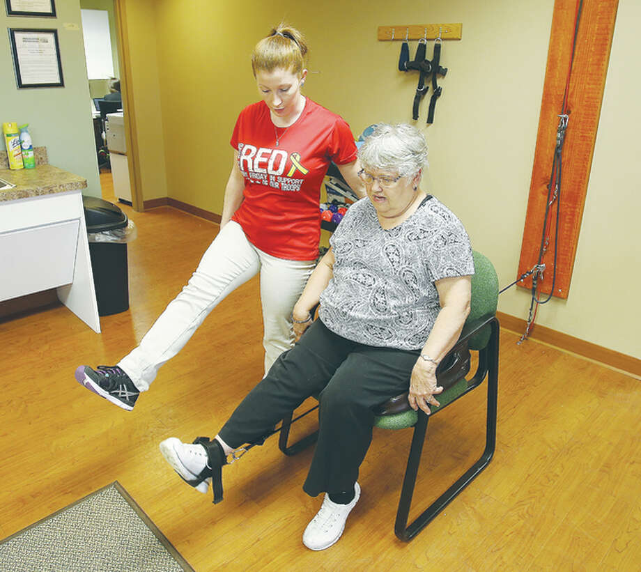 Physical therapy is a vital part of the treatment process at the Associated Physicians Group in Edwardsville. Here Physical Therapy Assistant Sara Aleandri, left, works with patient Bonnie Seitz to do leg lifting with an ankle weight. Photo: John Badman|The Telegraph