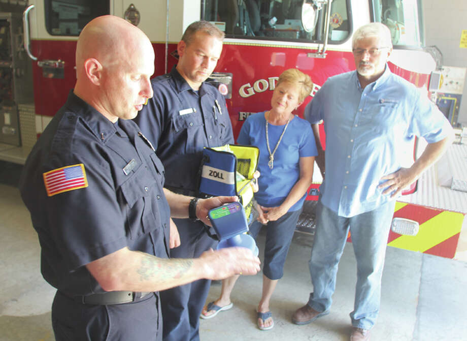 Eddie Knezevich (left), a Godfrey firefighter and EMT, talks with Doug Dankenbring, a firefighter and paramedic, and Jess and Ginger Woodman at the Godfrey Fire Protection District Station 1 on Thursday. The Woodmans recently donated a new CPR system to the district. Photo: Scott Cousins | The Telegraph