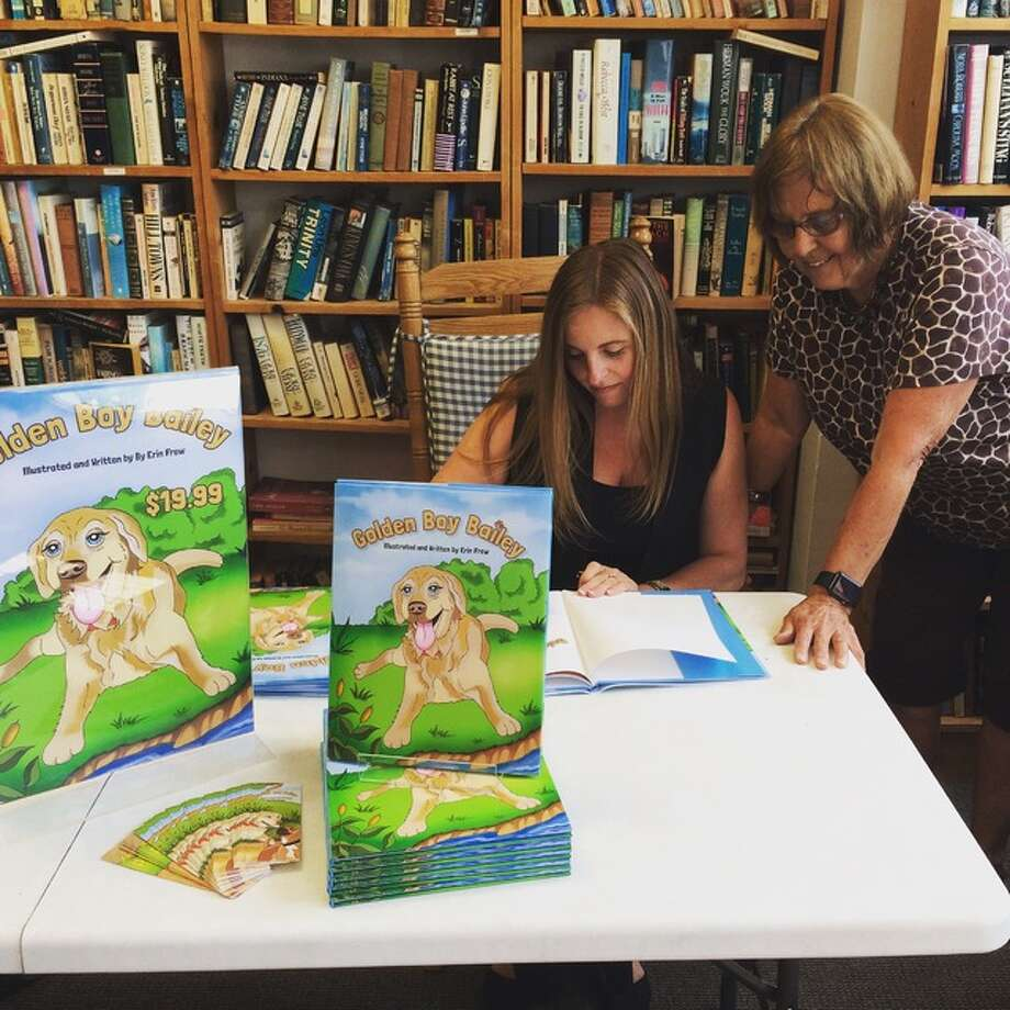 "Erin Frew signs a copy of her book ""Golden Boy Bailey,"" for Linda Barton at a recent signing at Second Reading Books in downtown Alton."