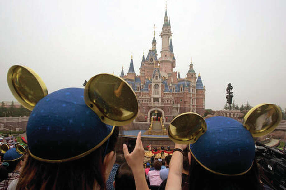 Visitors wearing Mickey hats take photos of Shanghai Mayor Han Zheng, left, Chinese Vice Premier Wang Yang, center, and Disney CEO Bob Iger preparing to cut the red ribbon during the opening ceremony for the Disney Resort in Shanghai, China, Thursday, June 16, 2016. Walt Disney Co. opened its first theme park in mainland China on Thursday at a ceremony that mixed speeches by Communist Party officials, a Chinese children's choir and actors dressed as Sleeping Beauty and other Disney characters. (AP Photo/Ng Han Guan) Photo: (AP Photo/Ng Han Guan)