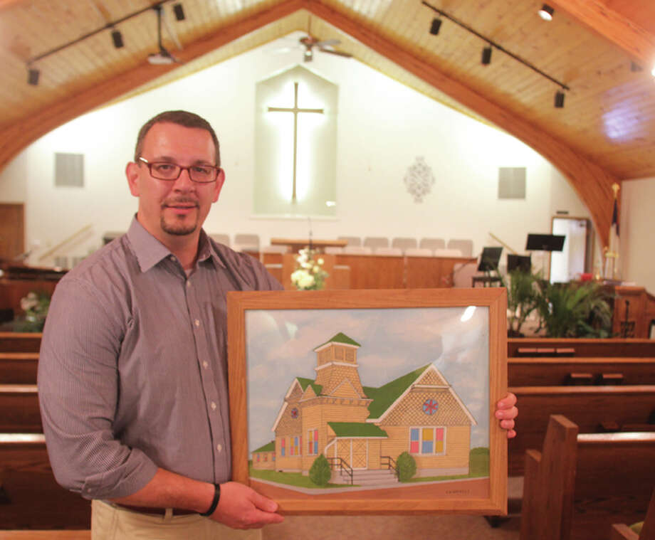 Rev. Ken Fields, pastor of Delhi Baptist Church, holds a painting of the original church building while standing in the present-day sanctuary. The church will celebrate its 125th anniversary next weekend.