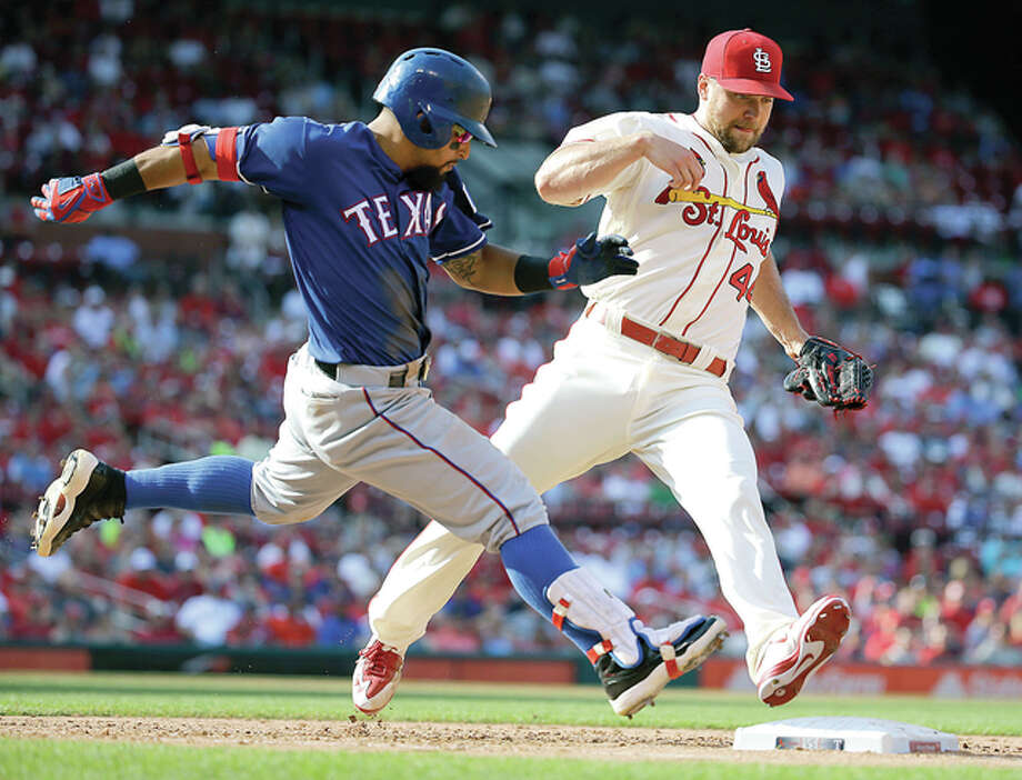 Texas Rangers' Rougned Odor, left, is safe at first as he beats Cardinals reliever Trevor Rosenthal to the bag in the ninth inning of Saturday's game in St. Louis. Photo: Jeff Roberson | AP Photo