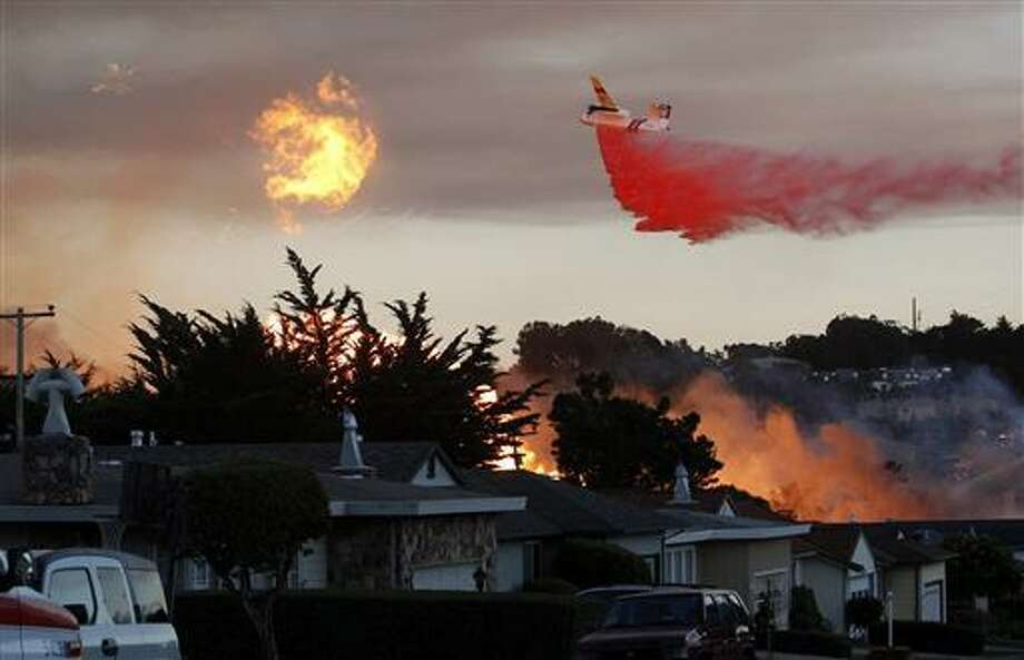 In this Sept. 9, 2010, file photo, a massive fire following a pipeline explosion roars through a mostly residential neighborhood in San Bruno, Calif. One of the country's largest utility companies is set to face a jury in a criminal trial accusing it of misleading investigators in the wake of a deadly pipeline explosion in the San Francisco Bay Area. The September 2010 blast of a Pacific Gas & Electric Co. natural gas pipeline sent a giant plume of fire into the air in a neighborhood in San Bruno, killing eight people and destroying 38 homes. Opening arguments in the trial began Thursday.