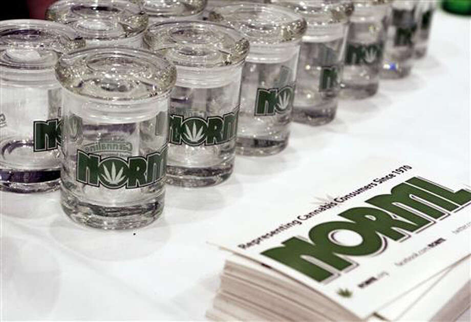 Glass marijuana containers bearing the logo for the National Organization for the Reform of Marijuana Laws, are displayed next to NORML promotional materials at the Cannabis World Congress and Business Exposition, Friday in New York. The three-day conference at New York City's Jacob K. Javits Convention Center was a gathering of professionals and advocates from nearly every facet of the emerging marijuana industry.