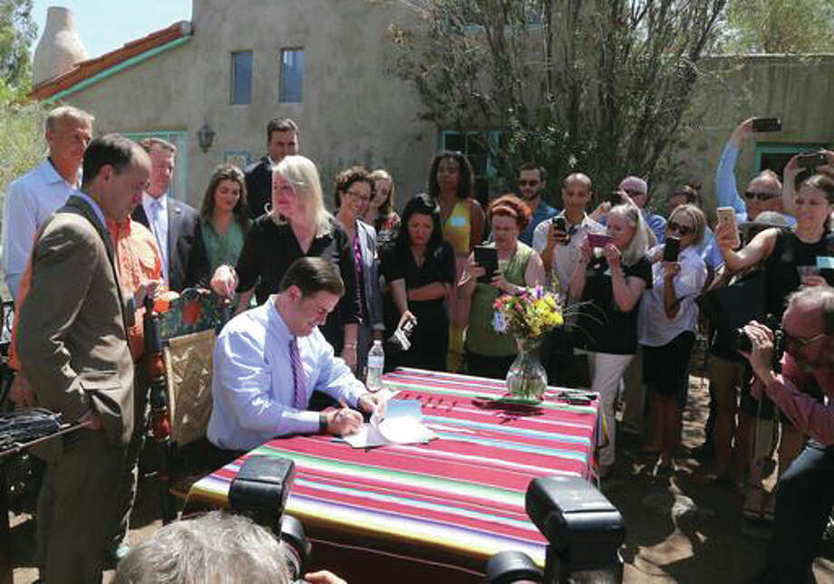 Arizona Gov. Doug Ducey, seated, holds a ceremonial signing in Phoenix, Ariz., Wednesday, June 1, for a new law that will make it easier for the state to gather home-sharing rental taxes while blocking cities from banning short-term rentals on lodging websites. Ducey met with vacation rental website executives from Airbnb and HomeAway, local hosts and lawmakers at a historic home.