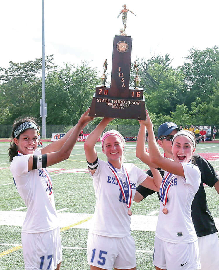 Marquette Catholic captains, from left, Adrianna Schindler, Bailey Hartrich and forward Lauren Schmickley hold up the Class 1A third-place trophy after beating Williamsville at North Central College. Photo: Sean King | For The Telegraph
