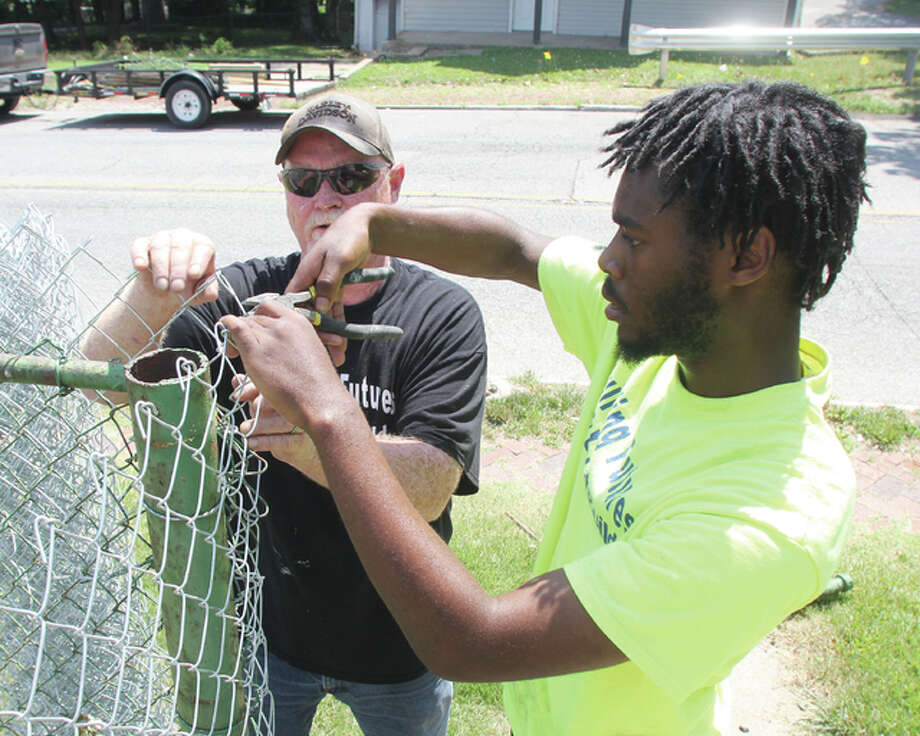 Andre Ewing, 18, of Alton, cuts a wire while installing a chain-link fence in a yard on Central Avenue Monday afternoon as instructor Mitch Fletcher watches. Ewing was participating in the YouthBuild AmeriCorps Central Avenue Beautification Project.