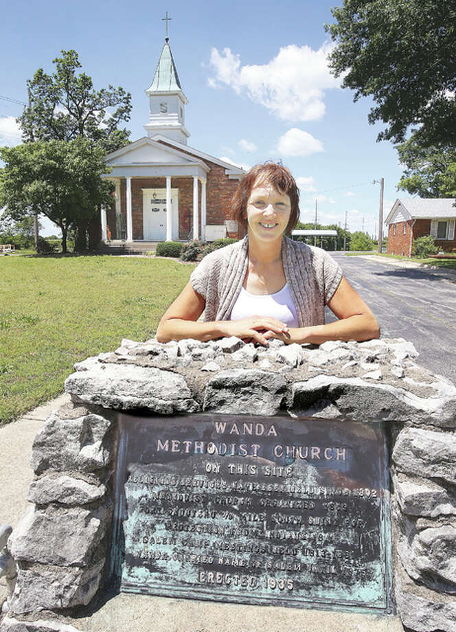 "Administrative Assistant Shelly Dalton at the historic Wanda United Methodist Church located in an area known as ""Wanda,"" tucked away on Old Edwardsville Road, between South Roxana and Edwardsville, stands by the marker that states the church has had a church building on the same site since 1802. The current church, background, was built in 1957, but a church has stood on the same spot for more than 200 years. Photo: John Badman