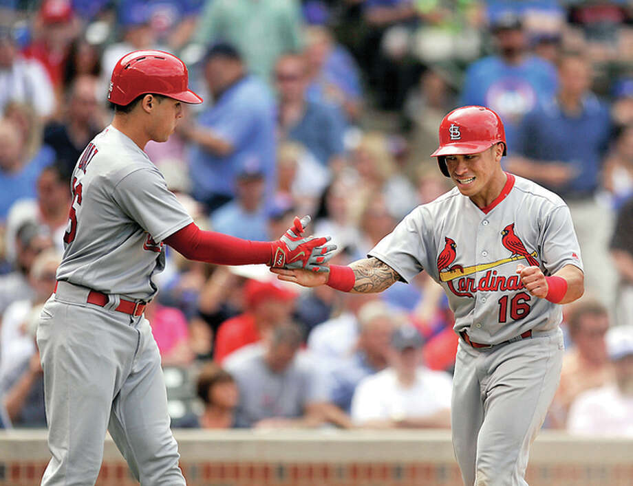 The Cardinals' Kolten Wong (16), celebrates with teammate Aledmys Diaz left, after scoring on a Matt Carpenter two-RBI double in the sixth inning Wednesday against the Cubs at Wrigley Field. Photo: AP Photo