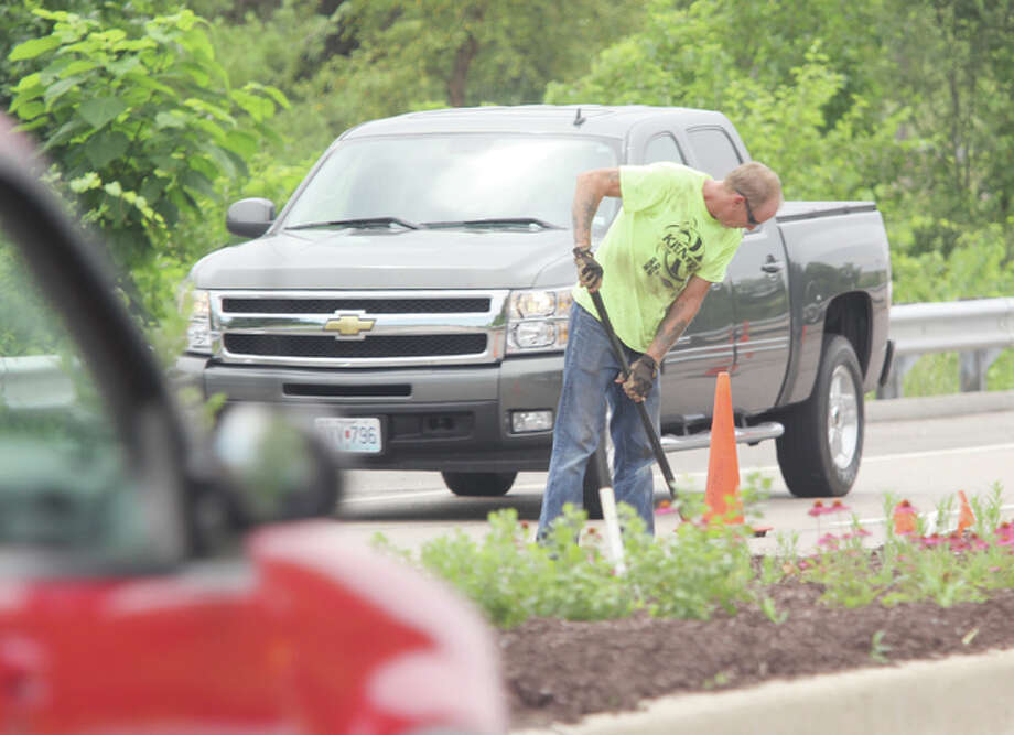An employee of RCS Construction Inc. of Wood River digs in the median on River Heritage Parkway (Illinois Route 143) near Discovery Parkway in Alton as part of the continuing, BridgeWest Corridor Beautification project as traffic passes nearby.