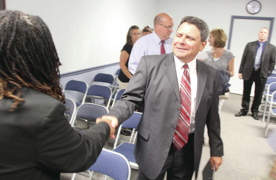 Mark Cappel, the newly appointed interim superintendent for the Alton School District, greets employees after Tuesday's board meeting. Cappel retired as director of human resources with the district last year.