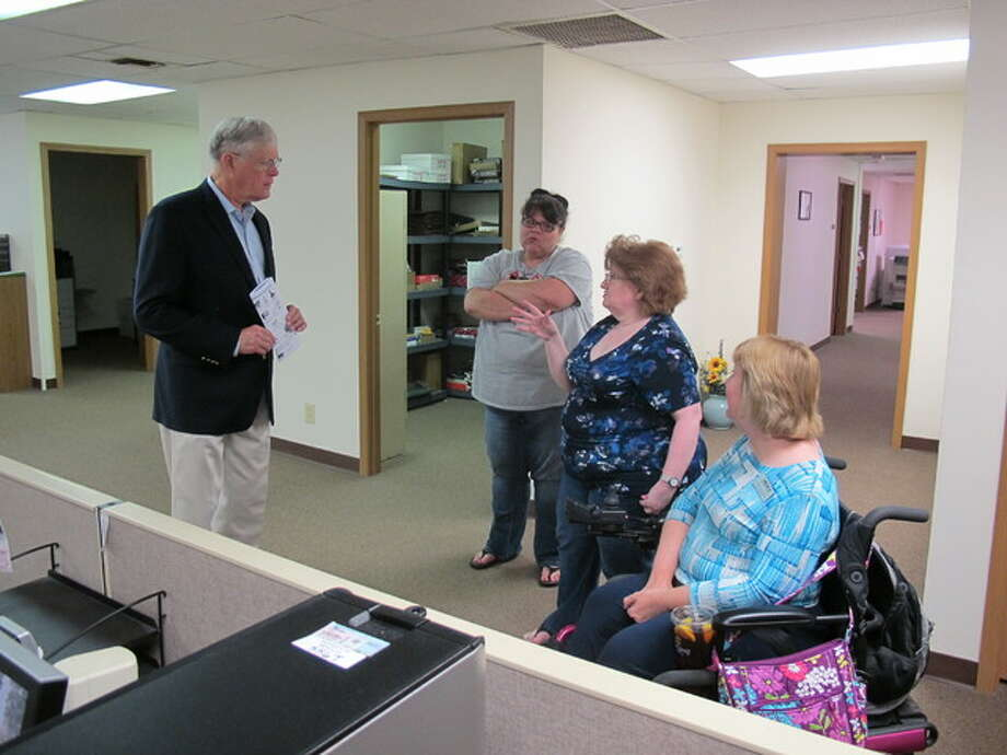 State Sen. Bill Haine visits with employees at Impact CIL in Alton Wednesday.