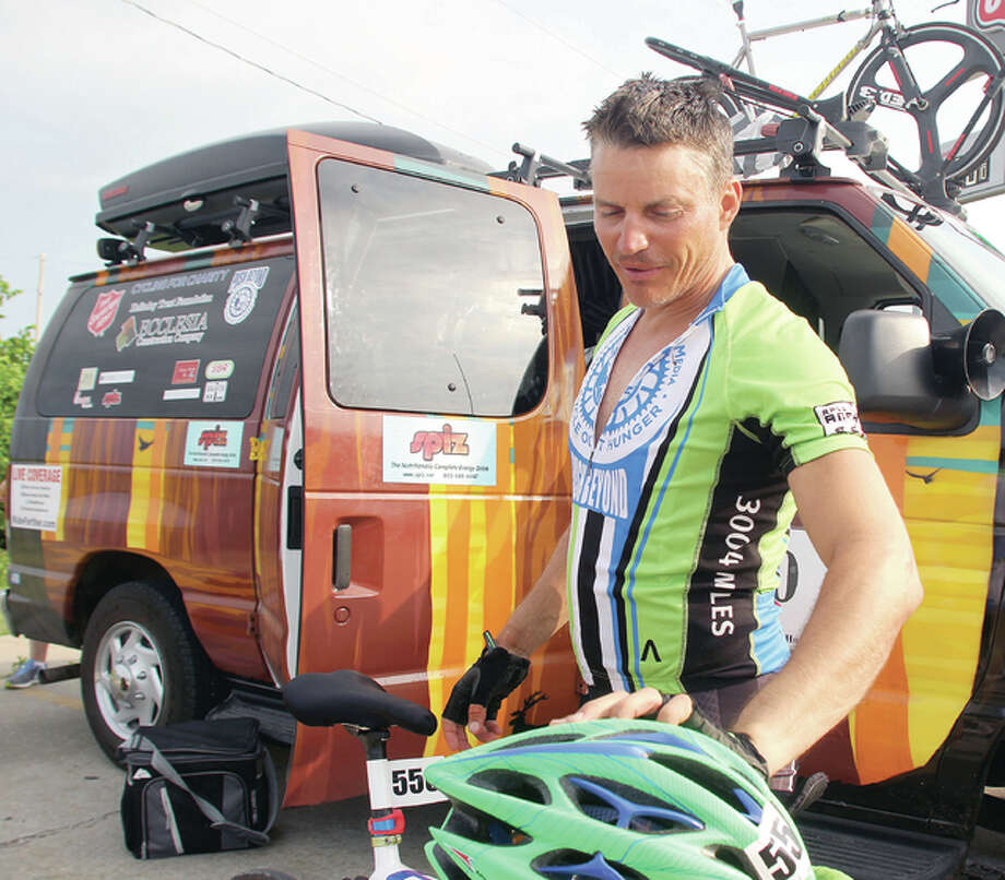 Marshall Nord checks out his helmet as he prepares to get back on his bicycle and continue with the Race Across America, which began earlier this month in Riverside, California and will end in Annapolis, Maryland. He is a native of Alton, now living in York, South Carolina. Photo: Scott Cousins | The Telegraph