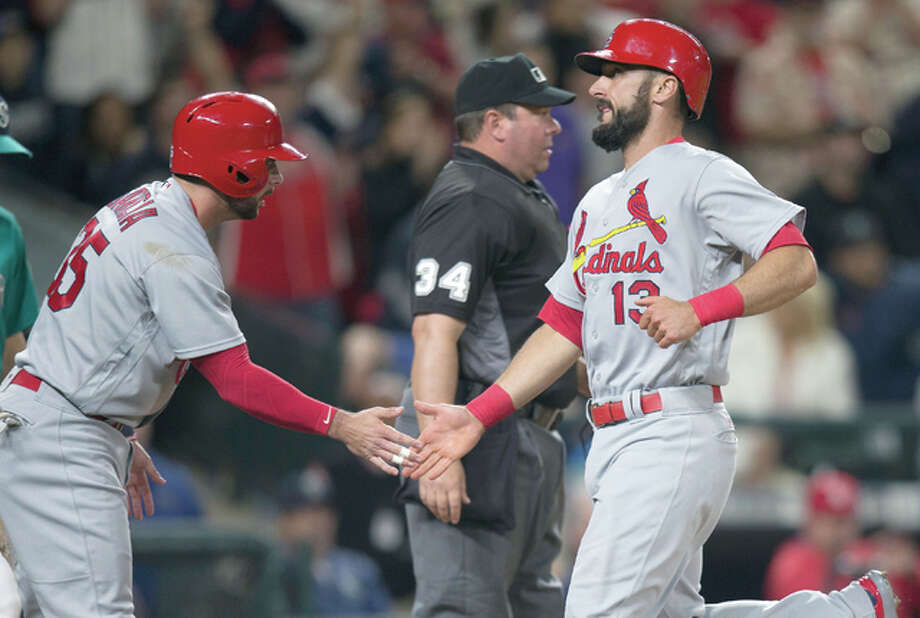 The Cardinals' Greg Garcia, left, congratulates teammate Matt Carpenter after Carpenter and Garcia scored on a bases-loaded single by Matt Holliday in the eighth inning Friday night in Seattle. Photo: Stephen Brashear | AP Photo