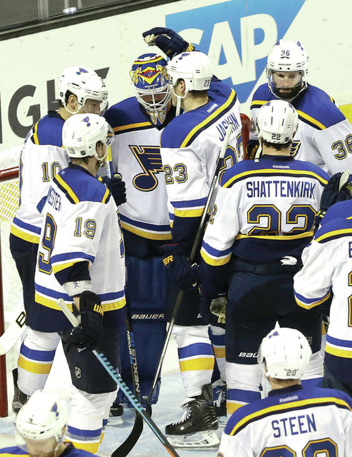 Elliott Blues players gather around goalie Brian Elliott (top center) after the Blues lost to the San Jose Sharks in Game 6 of the NHL Stanley Cup Western Conference finals. The Blues traded Elliott to Calgary Friday. Photo: AP