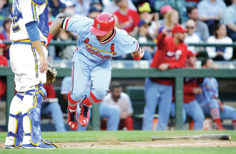 The Cardinals' Kolten Wong jumps at home after reaching for a bat, but missing, as he scored against the Mariners in the third inning Saturday's game in Seattle.