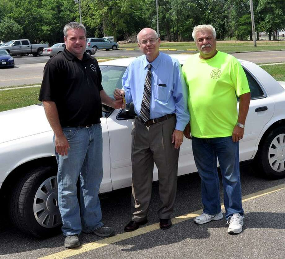 Long Lake Fire Chief Terry Kreher, Madison County Chairman Alan Dunstan and Long Lake Fire Department President Alan Naney are pictured with one of the vehicles recently sold by the county. Long Lake FD was able to purchase the vehicle for $1 through a program initiated by the board.