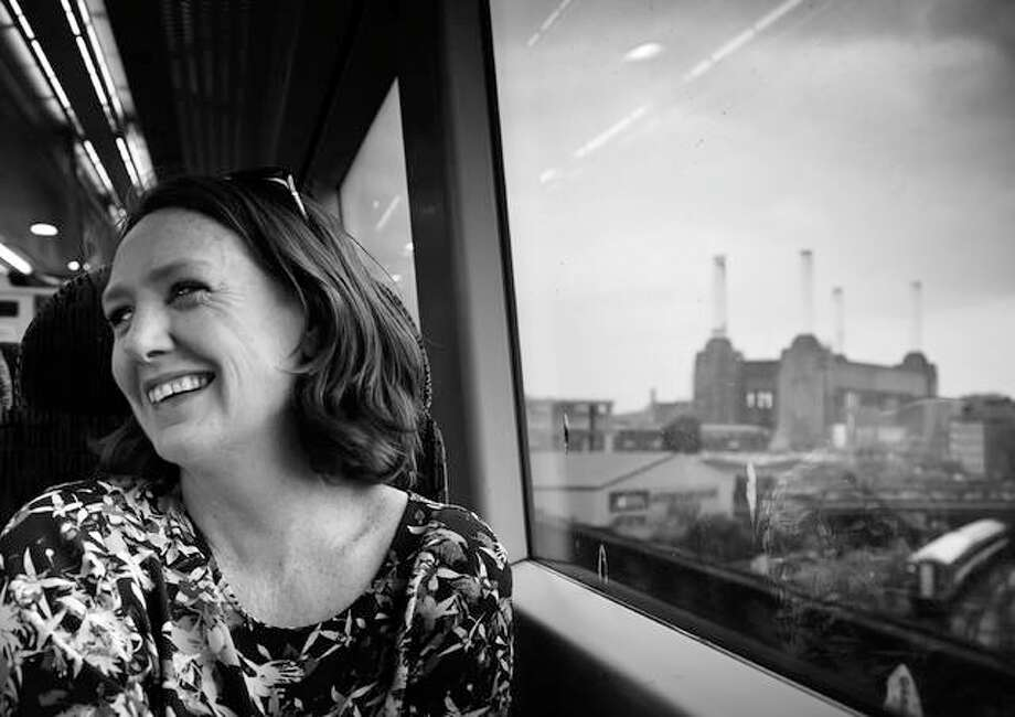"Paula Hawkins, author of ""The Girl on the Train,"" while sitting on a train with an urban view that might be close to what the protagonist in the story witnessed on a daily basis. For The Telegraph"